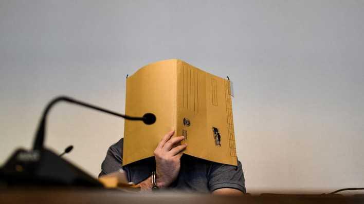 Baden-Württemberg, Freiburg: Der wegen Kindesmissbrauchs angeklagte Mann sitzt im Gerichtssaal und hält einen Aktendeckel vor sein Gesicht